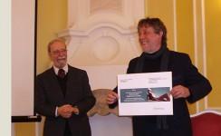 Dem Bildhauer Thomas Reimann (r.) wird der Auftrag für das Brigitte-Reimann-Denkzeichen übergeben.