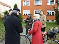 Jedssica Jenkins, mit Fahrrad, vor dem ehemaligen Wohnhaus von Brigitte Reimann in Hoyerswserda im Gespräch mit Martin Schmidt und der Presse.